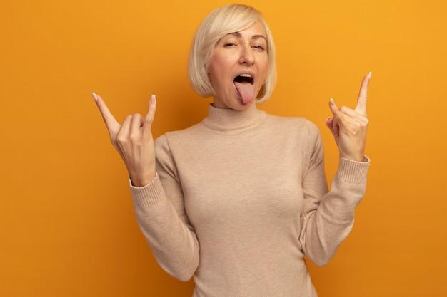 즐거운 예쁜 금발의 슬라브 여자가 오렌지에 두 손으로 혀를 내밀고 뿔을 몸짓으로 표시합니다.