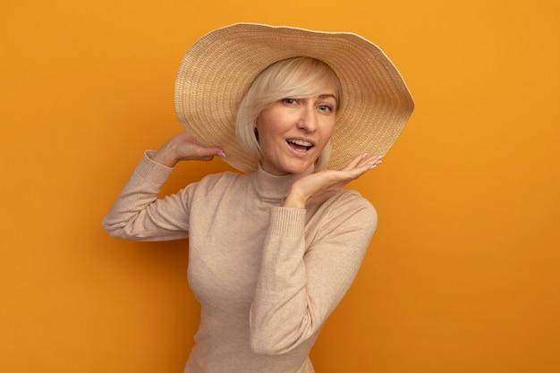ビーチ帽子をかぶったうれしそうなきれいな金髪のスラブ女性は、オレンジ色の壁に隔離された手を開いて保持します。