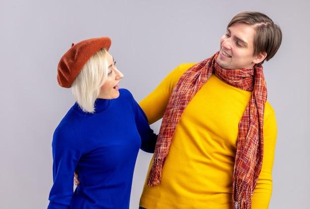 ベレー帽と彼の首の周りにスカーフと笑顔のハンサムなスラブの男とうれしそうなきれいなブロンドの女性は、コピースペースで白い壁に隔離された上でお互いを見てください