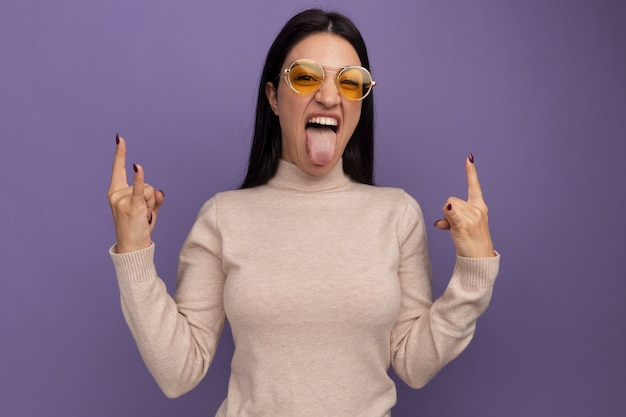 Радостная симпатичная кавказская девушка в солнцезащитных очках высунула язык и жестикулирует двумя руками на фиолетовом