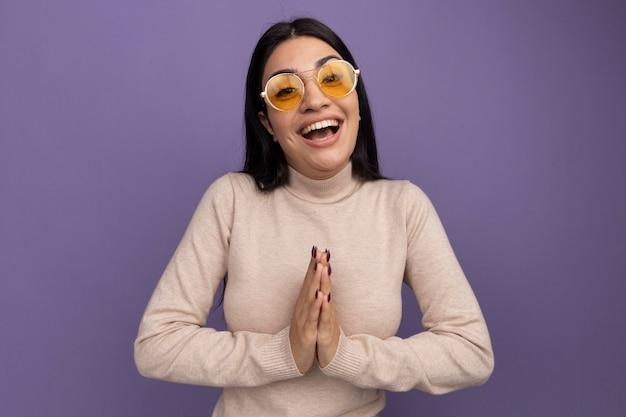 La ragazza caucasica del brunette graziosa gioiosa in occhiali da sole tiene le mani insieme sulla porpora