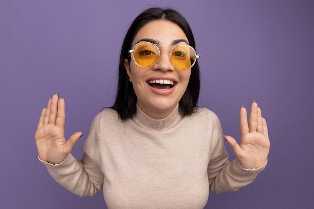 La ragazza caucasica del brunette graziosa gioiosa in occhiali da sole sta con le mani alzate sulla porpora