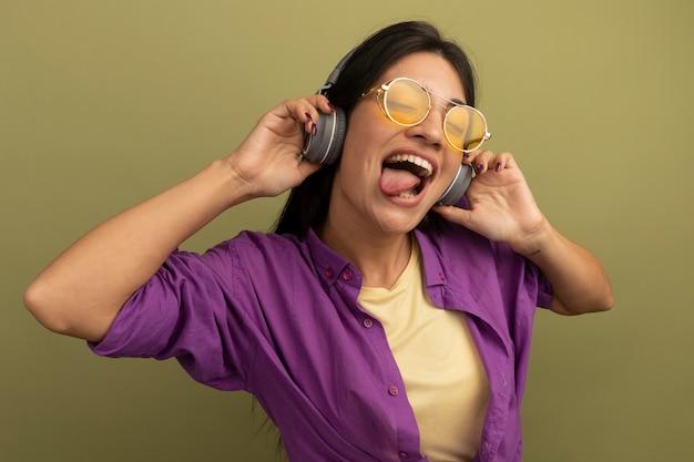 Ragazza caucasica bella mora gioiosa in occhiali da sole con le cuffie sporge la lingua su verde oliva