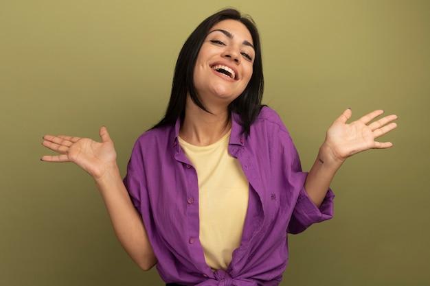 Donna caucasica castana graziosa allegra che sta con le mani alzate isolate