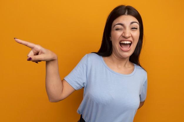 La donna graziosa gioiosa del brunette indica al lato isolato sulla parete arancione
