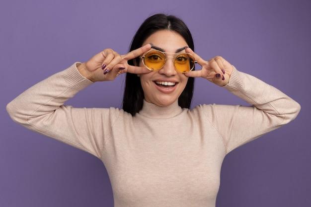 Gioiosa bella donna castana in occhiali da sole gesti il segno della mano di vittoria con due mani isolate sulla parete viola