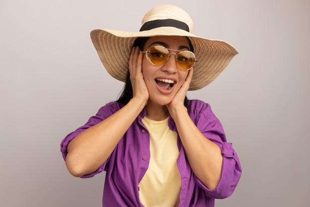 Gioiosa bella donna castana in occhiali da sole con cappello da spiaggia mette le mani sul viso isolato sul muro bianco