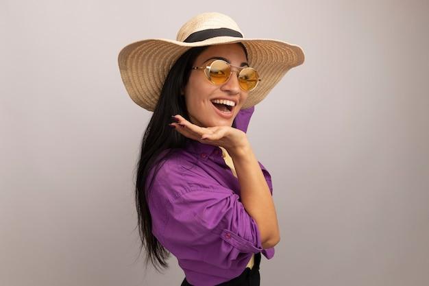 Gioiosa bella donna castana in occhiali da sole con cappello da spiaggia si leva in piedi lateralmente mette la mano sul mento isolato sul muro bianco