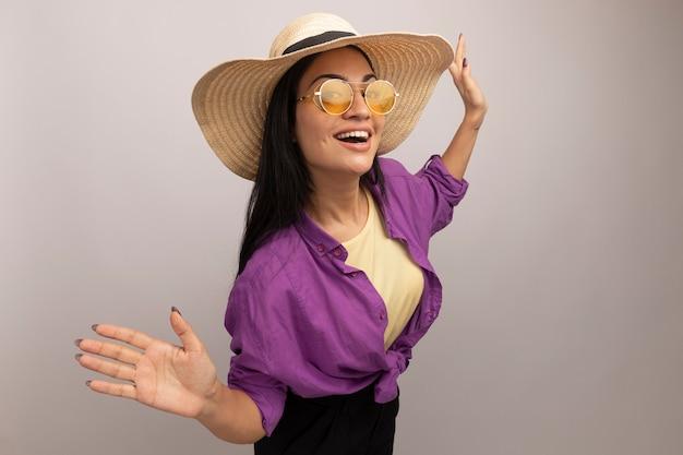 Gioiosa bella donna castana in occhiali da sole con cappello da spiaggia sta con le mani alzate guardando la parte anteriore isolata sul muro bianco