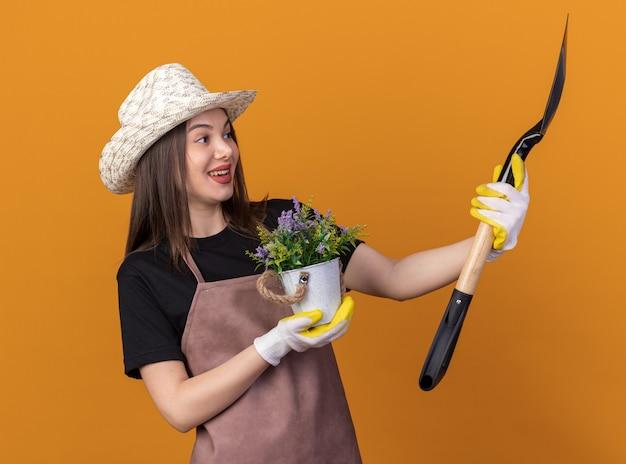 Giardiniere femminile abbastanza caucasico allegro che indossa cappello e guanti di giardinaggio che tengono vaso di fiori e che esamina vanga isolato sulla parete arancione con lo spazio della copia