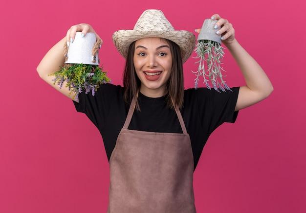 コピースペースとピンクの壁に分離された植木鉢を逆さまに保持しているガーデニング帽子をかぶっているうれしそうなかなり白人女性の庭師