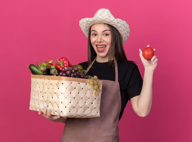 野菜のバスケットとトマトを保持しているガーデニング帽子をかぶってうれしそうなかなり白人女性の庭師