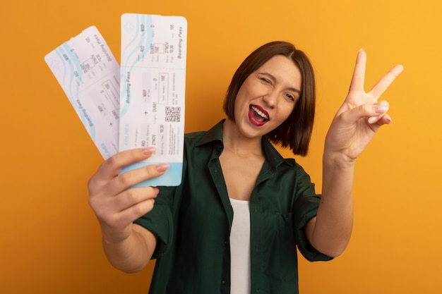 Joyful pretty caucasian woman blinks eye and gestures victory hand sign holding air tickets on orange