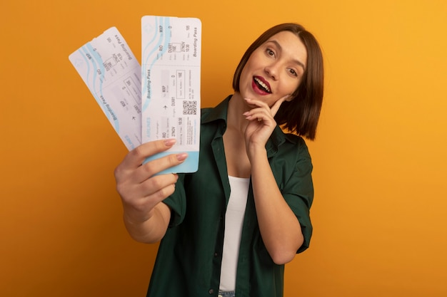 Joyful pretty caucasian woman puts hand on face and holds air tickets on orange