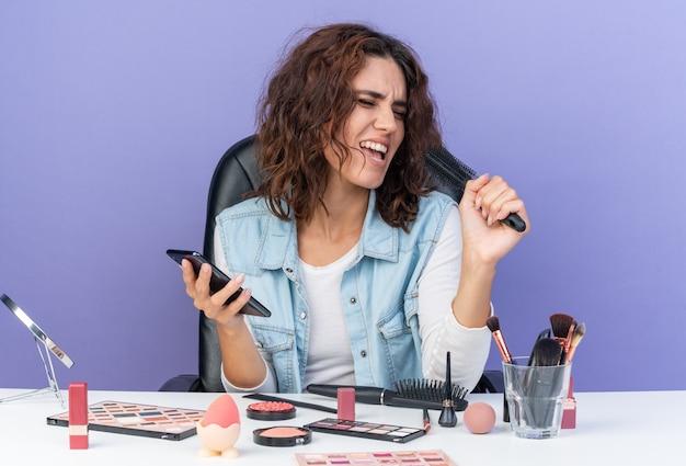 전화와 빗을 들고 있는 화장 도구를 들고 테이블에 앉아 있는 즐거운 백인 여성은 복사 공간이 있는 보라색 벽에 고립되어 노래하는 척