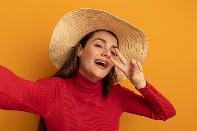 Gioiosa donna abbastanza caucasica con cappello da spiaggia gesti il segno della mano di vittoria e finge di tenere la fotocamera sull'arancio