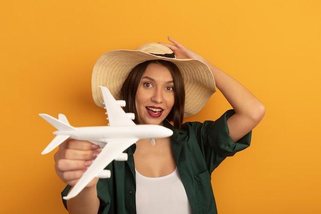 ビーチ帽子をかぶったうれしそうなかなり白人女性はオレンジ色の模型飛行機を保持します