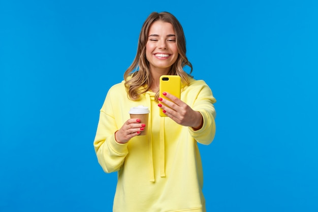Joyful pretty feminine blond short-haired woman in yellow hoodie, taking selfie with take-away coffee from favorite local cafe, smiling smartphone standing with mobile phone