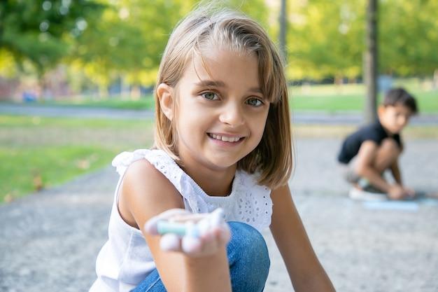 Радостная красивая девушка сидит и рисует на бетоне, держа в руке разноцветные мелки. снимок крупным планом. концепция детства и творчества