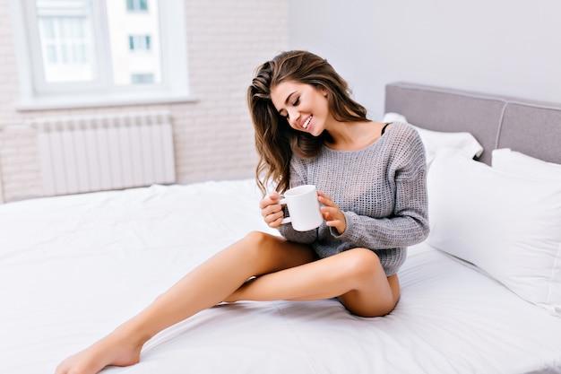Радостная симпатичная девушка с длинными волосами брюнетки отдыхает на белой кровати по утрам. веселая модель в вязаном свитере с длинными голыми ногами пьет кофе в современной квартире. отдых, красота, хорошее настроение.