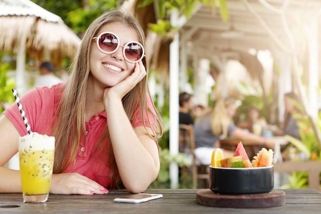 Gioiosa bella signora che indossa eleganti occhiali da sole rotondi, seduto al bar con cocktail, frutta e telefono cellulare sul tavolo di legno, appoggiato sul gomito e guardando con un sorriso allegro e felice, godendo le vacanze