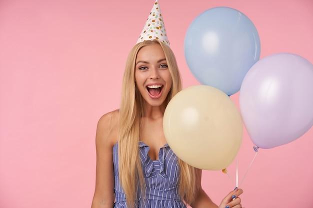 Радостная довольно длинноволосая блондинка с веселыми моментами в жизни во время дня рождения, позирует на розовом фоне с разноцветными воздушными шариками, пребывая в приподнятом настроении