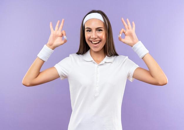 紫色の壁に分離された ok の標識をしているヘッドバンドとリストバンドを身に着けているうれしそうなかなりスポーティな女の子