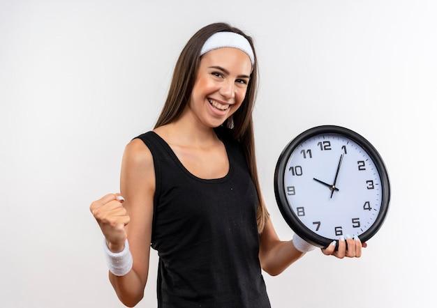 Радостная симпатичная спортивная девушка с ободком и браслетом держит часы со сжатым кулаком, изолированными на белой стене