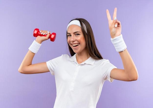 Радостная симпатичная спортивная девушка с повязкой на голову и браслетом с гантелями делает знак мира на фиолетовой стене
