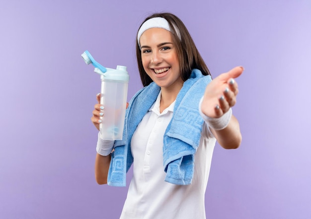 ヘッドバンドとリストバンドを身に着け、水のボトルを持ち、紫色の壁に隔離された首にタオルで手を伸ばすうれしそうなかなりスポーティな女の子