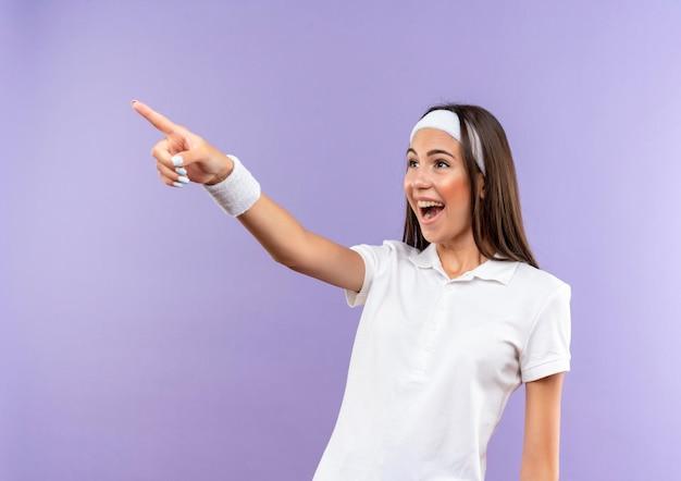 ヘッドバンドとリストバンドを着て、紫色の壁に隔離された側を指して見て、うれしそうなかなりスポーティな女の子