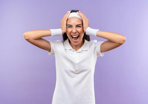 Радостная симпатичная спортивная девушка с повязкой на голову и браслет, положив руки на голову, изолированную на фиолетовой стене