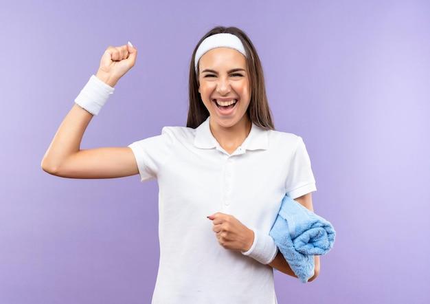 Gioiosa ragazza abbastanza sportiva che indossa fascia e cinturino che tiene asciugamano e alza il pugno isolato sul muro viola