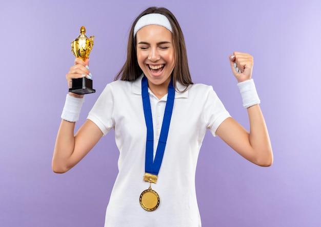 Gioiosa ragazza abbastanza sportiva che indossa fascia e cinturino e medaglia che tiene la tazza alzando il pugno con gli occhi chiusi isolati sul muro viola
