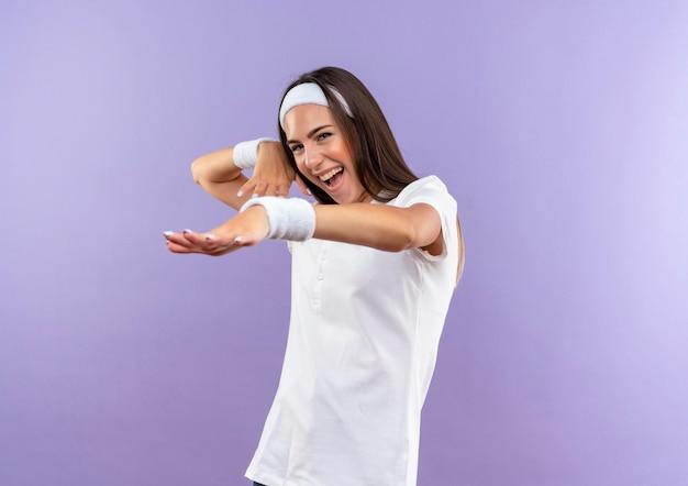 Gioiosa ragazza abbastanza sportiva che indossa fascia e braccialetto che allungano la mano con un'altra vicino alla testa isolata sul muro viola