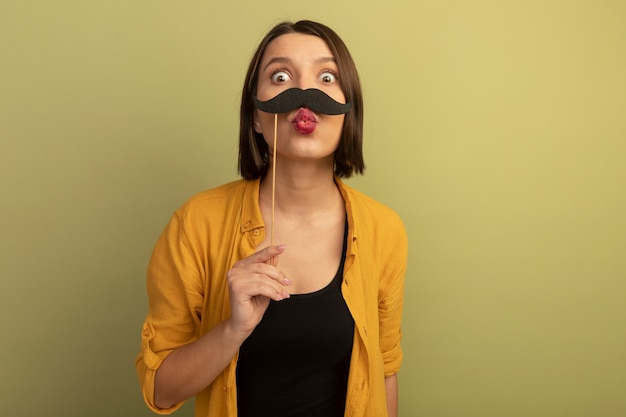 うれしそうなきれいな女性は、オリーブグリーンの壁で隔離の棒に偽の口ひげを保持