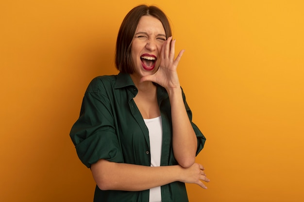 La donna graziosa allegra tiene la mano vicino alla bocca che chiama qualcuno isolato sulla parete arancione