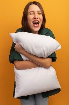 うれしそうなきれいな女性はオレンジ色の壁に分離された枕を保持します