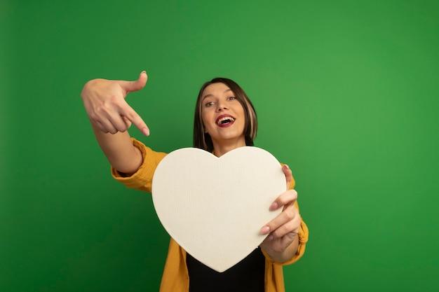 La donna graziosa allegra tiene e indica la forma del cuore isolata sulla parete verde