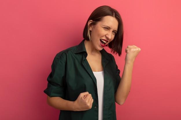 즐거운 예쁜 여자는 분홍색 벽에 고립 된 정면을보고 주먹을 유지