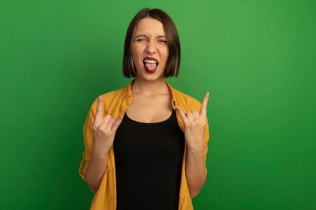 Радостная симпатичная женщина высунула язык и жестом жестом показывает знак рукой рогами двумя руками, изолированными на зеленой стене
