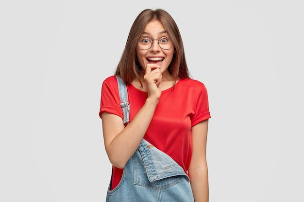 うれしそうなきれいな女性は丸い眼鏡をかけ、顎に手を保ちます
