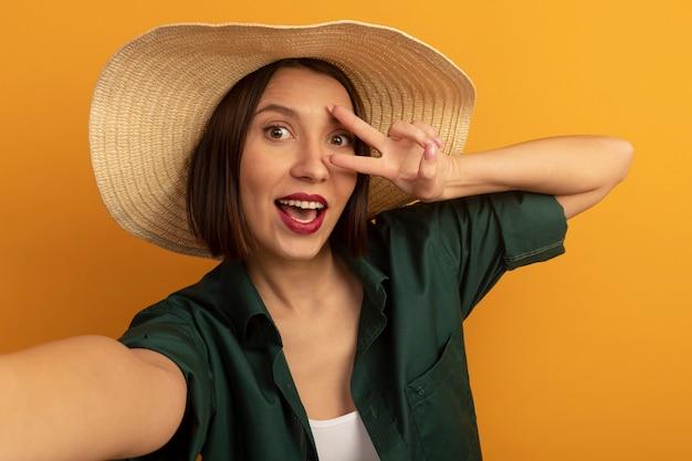 Donna graziosa allegra con il segno della mano di vittoria di gesti del cappello della spiaggia isolato sulla parete arancio