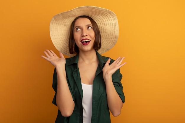 ビーチ帽子をかぶったうれしそうなきれいな女性は、オレンジ色の壁に隔離された手を開いて保持します。