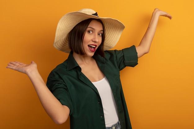 ビーチ帽子を持つうれしそうなきれいな女性は、オレンジ色の壁に分離された上げられた手で立っています