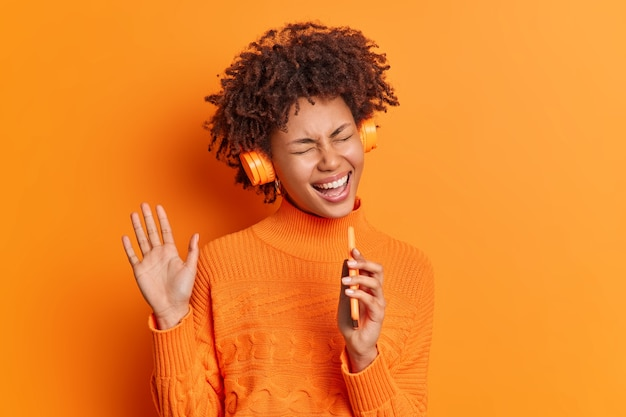 곱슬 머리를 가진 즐거운 예쁜 여자는 헤드폰에서 재미를 가지고 스마트 폰에서 좋아하는 음악 노래를 듣고 손을 들어 생생한 오렌지 벽 위에 절연 캐주얼 스웨터를 착용