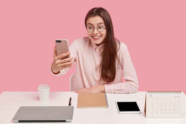 Gioiosa bella donna con un sorriso piacevole, tiene il cellulare davanti al viso, vestita con una camicia elegante, fa una videochiamata, felice di notare un amico a distanza