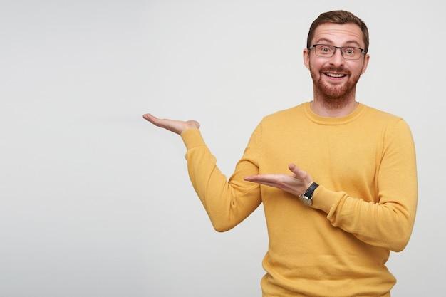 Gioioso piuttosto giovane brunetta uomo barbuto con taglio di capelli corto rivolto a parte con i palmi e sollevando felicemente le sopracciglia mentre guarda, isolato
