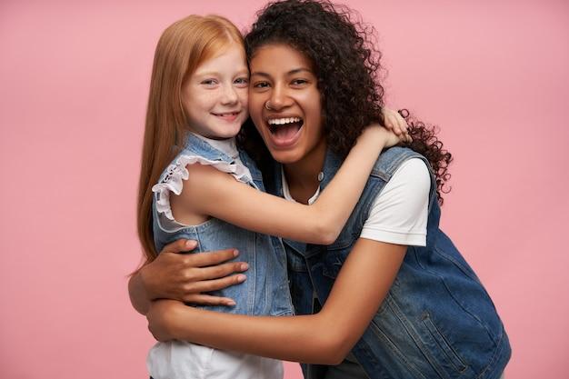 鼻ピアスが楽しく笑い、ピンクに立ち向かう小さな素敵な赤毛の女の子を優しく抱きしめている、うれしそうなかなり若い暗い肌の巻き毛のブルネットの女性