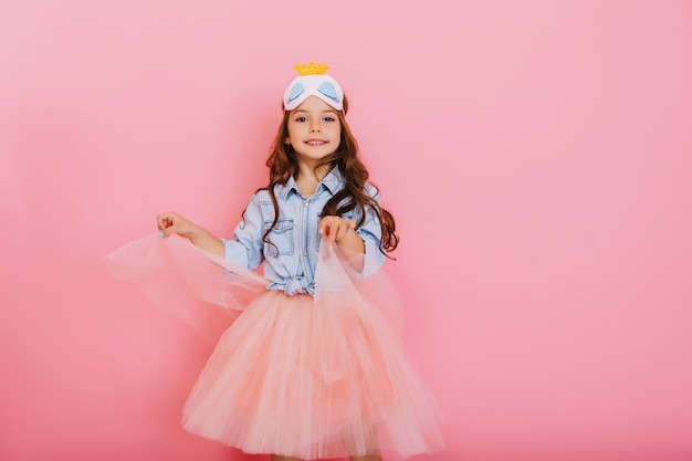 Joyful pretty young girl with long brunette hair dancing in tulle skirt isolated on pink background. amazing cute little princess with mask on head smiling, expressing positivity to camera